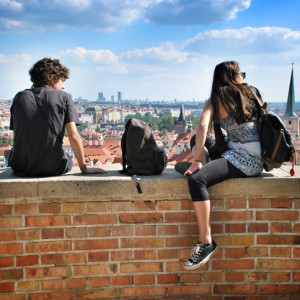 Молодые люди сидят на кирпичной стене