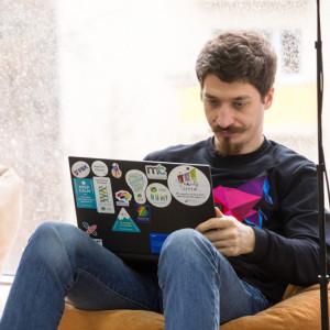 Мужчина с ноутбуком на пуфике