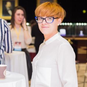 Девушка в белой блузке с короткими рыжими волосами