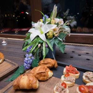 Букет искусственных цветов рядом с закусками
