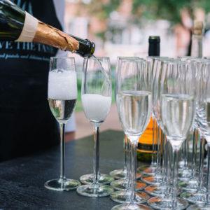 официант наливает шампанское в бокалы