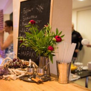 Бокал шампанского и кувшин с цветами на барной стойке