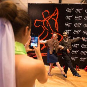 Танцоры позируют на фоне пресс волла