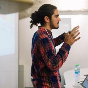 парень в клетчатой рубашке ведет презентацию