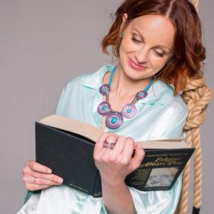 рыжая девушка читает книгу и улыбается