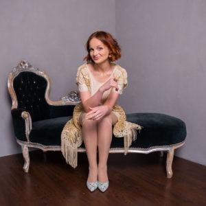 девушка в платье сидит на кушетке