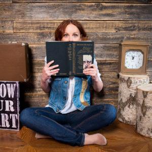 девушка в джинсовом костюме держит в руках книгу