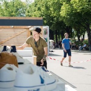 молодой человек выставляет обувь на витрину выставочного стенда