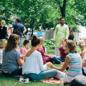 группа людей медитирует в парке на зеленой траве