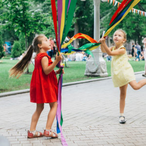 девочки в платьицах играют с лентами