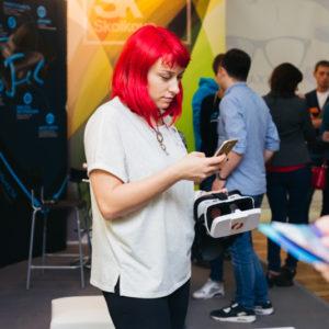 девушка с красными волосами и VR очками в руке