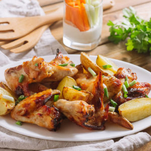 Картофель с овощами и крыльями | Oval white plate with fried chicken wings with fried potatoes. Food sprinkled with chopped scallion. Against the background is a glass with chopped carrots and celery in sour cream. Parsley branch.