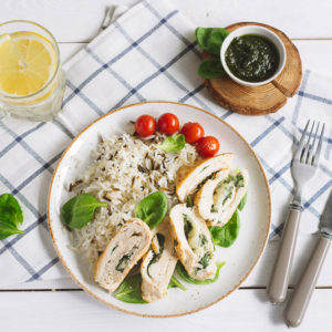 Куриное филе с рисом, шпинатом и овощами | Chicken fillet roll with spinach. Garnished with long-grain wild rice. Cherry tomatoes, pesto sauce, a glass of water and a slice