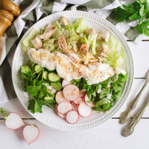 Салат айсберг, курицей и овощами | Iceberg salad with square slices of chicken fillet, chopped cucumber, parsley, radish, sour cream and sprinkled with blanched peanut slices. Wooden pepper mill.
