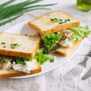 Тосты с свиной шеей и сыром | White wheat bread toasted sandwich with pork meat and cheese, salad and sour cream. Chopped chives, bottled olive oil, a knife and a fork. Against the background of a gray fabric napkin.