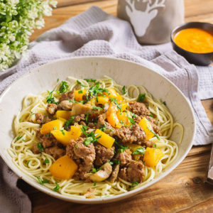 Яичная лапша с грибами и домашним фаршем | Deep plate with spaghetti, minced meat, chopped parsley, yellow bell pepper. Nearby is a bowl with sauce, a fork and a knife, a table napkin, a kitchen waffle towel. Serving per person.