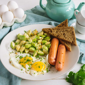 Яйца с сосисками и кабачком | Fried eggs for breakfast on a white plate. Fried eggs with sausages and zucchini, two slices of rye bread, parsley. White wooden background and blue fabric napkin.