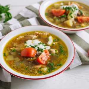 суп с курицей,чечевицей и сметаной | Two plates of chicken soup with vegetables, lentils and sour cream. Large slices of tomato and chopped parsley. On a white wooden table and a kitchen towel.