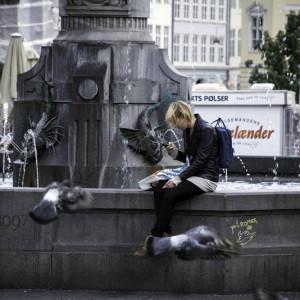 Девушка сидит на фонтане