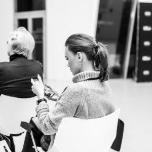 Девушка с телефоном в руках сидит на белом стуле