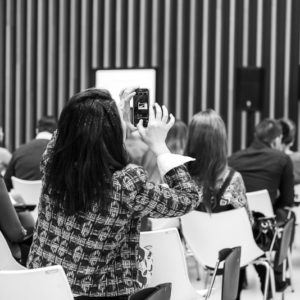 Девушка из аудитории фотографирует презентацию