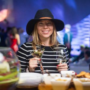 Девушка на вечеринке в шляпе и с бокалом белого вина